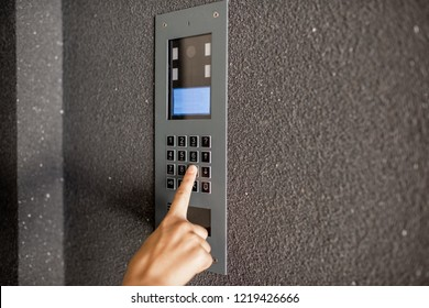 Close-up of intercome keyboard of residential building with finger entering code