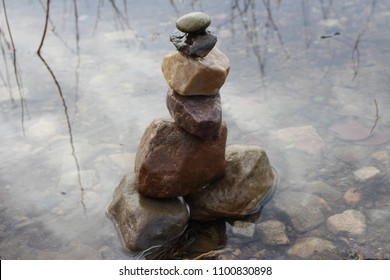 Close-up Inuksuk. Piled Stones on River Shore in Northern New York State at a camping site.