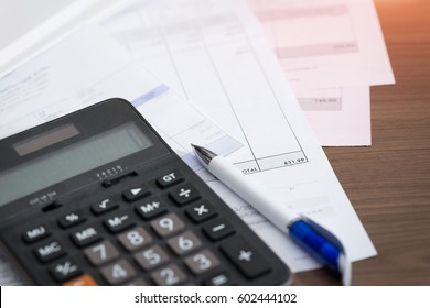 Close-up of invoice with calculator and pen. Pay the bills.