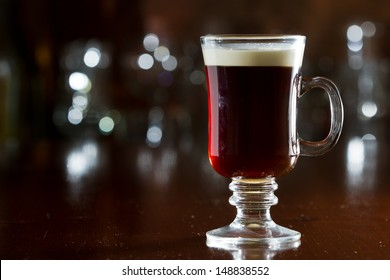 closeup of an irish coffee saved on a dark bar with a float of heavy cream