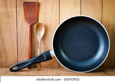 Closeup of  iron frying pan and wooden utensils on wood wall background .