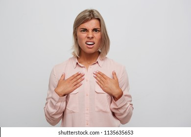 Closeup of irritated displeased blonde young woman with braces on teeth wears pink shirt feels confused and points at herself by hands isolated over white background