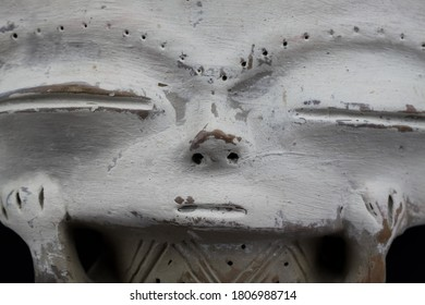 Closeup of isolated abstract inca clay figure with rectangular head and white face from Peru. Black background. (focus on center)