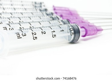 Closeup, Isolated disposable syringe in the row on white background