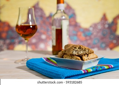 Closeup of Italian cantucci biscuits over a blue napkin and vin santo wine on background