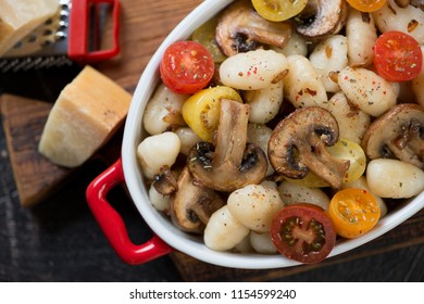 Close-up of italian gnocchi with fried champignons and fresh sliced tomatoes, view from above, horizontal shot