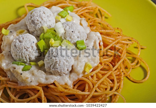 Close-up of an Italian pasta with white sauce and meatballs in a green plate.