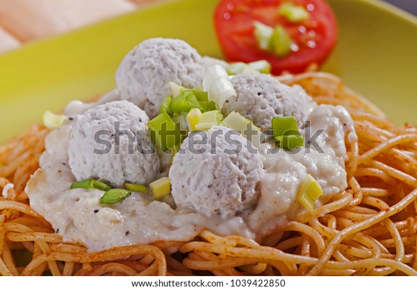 A close-up of an Italian pasta with white sauce, cherry tomatoes and meatballs in a green plate.