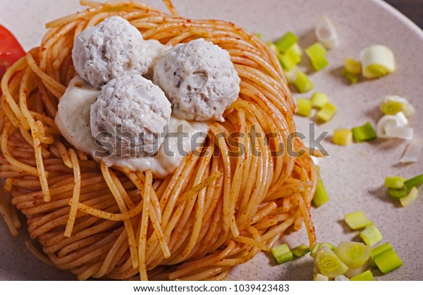 A close-up of an Italian pasta with white sauce, cherry tomatoes and meatballs on a white plate.