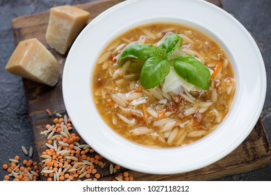 Close-up of italian soup with red lentil, pasta and addition of parmesan served in a white plate, studio shot, selective focus