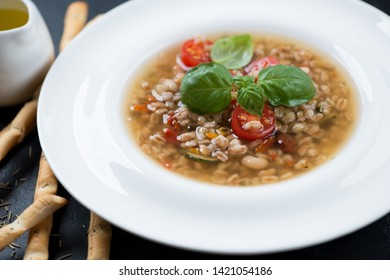 Close-up of italian spelt and vegetable soup served in a white plate, selective focus