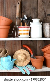 Closeup of items on the shelves of a potting shed. The rustic interior is full of flower pots, and other accessories and tools used in everyday gardening.