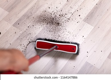 Close-up Of A Janitor Cleaning Dirt With Broom On Hardwood Floor