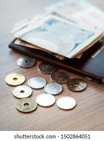 Closeup of Japanese coins, wads of banknote and foreigner passport laying on the table. Travel in Japan, Money currency, Yen, Cash-based society, VAT refund, Tax free, Expenses, Traveler, Tokyo 2020.