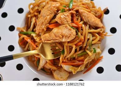 Closeup of Japanese famous foods in white plate.Yakisoba. Stir-fried noodles with chicken and vegetables.Enjoy eating using fork.Concept about homemade cooking delicious dishes at home with happieness