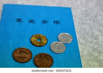 Close-up of Japanese pension book and coins. translation: pension book  Japan  1990 japan  10 yen 1995  one yen japan