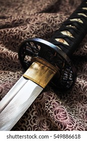 close-up japanese sword katana on satin with warm fall colors, soft-focus in the background. over light