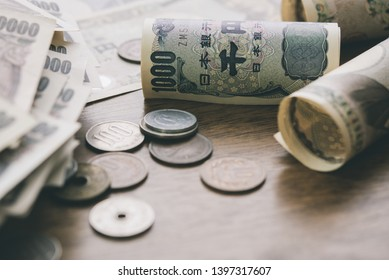 Closeup of Japanese yen money bills and coins on wood table background for financial concept