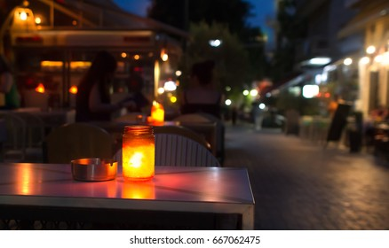 Closeup of a jar with a candle on a table with an ashtray, placed outside a bar at a pedestrian street in Greece. Summer evening.