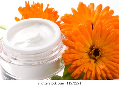 Closeup of jar of moisturizing face cream and fresh marigold flower
