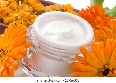 Closeup of jar of moisturizing face cream surrounded by fresh marigold flowers