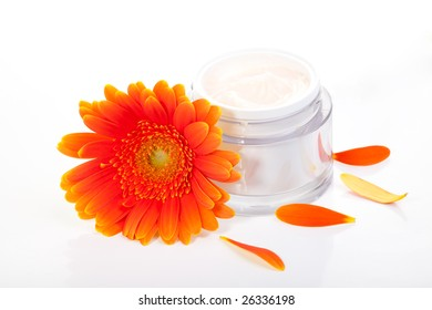 Closeup of jar of moisturizing face cream surrounded by orange gerbera flowers
