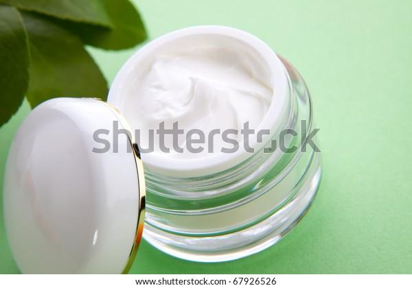 Closeup of jar of moisturizing face cream and fresh citrus