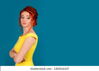 Close-up of a jealous unhappy beautiful young woman looking over her shoulder at someone. Caucasian person in yellow dress, redhead hair up isolated on blue studio background. Expressive face emotion.