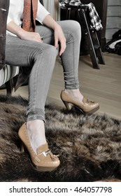 Close-up of jeans on legs model. She is dressed in a black tight-fitting jeans, a white shirt and a suede coat.