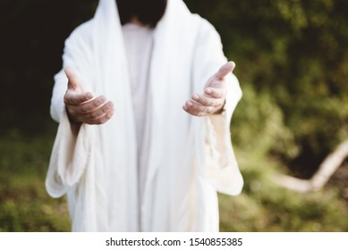 A closeup of Jesus Christ reaching out with a blurred background