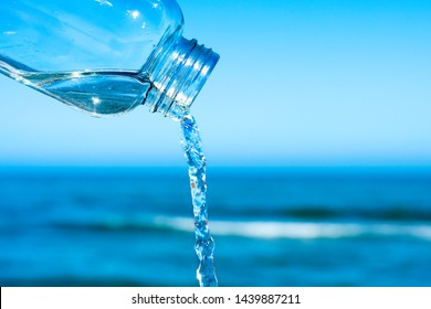 closeup of a jet of water flowing out of an almost empty reusable bottle, with the ocean in the background