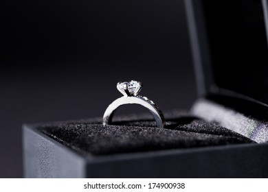 Close-up of a jewelry box with two elegant silver rings from which one with a diamond, symbol of engagement and elegance
