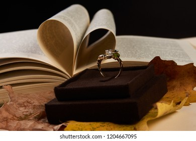 Close-up Jewelry gold diamond ring on autumn foliage and open book pages in heart shape as background with copy space.Elegant engagement diamond ring as  love and wedding concept, close-up.