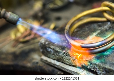 Close-up of jewelry welding with blowtorch. Goldsmith's workshop.