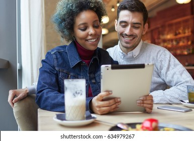 Closeup of joyful African American female and European Caucasian man sitting in cafe next to window, watching together media content on display of tablet computer with pleasure and happy smiles.