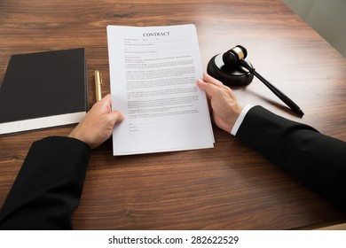 Close-up Of Judge Holding Contract Paper At Desk