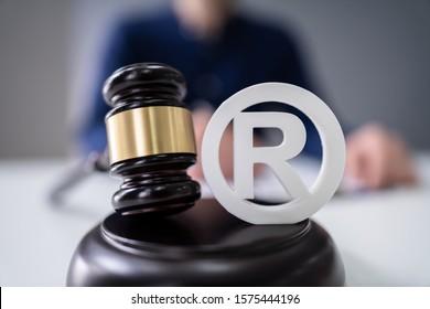 Close-up Of Judge Striking Mallet On Trademark Copyright Symbol