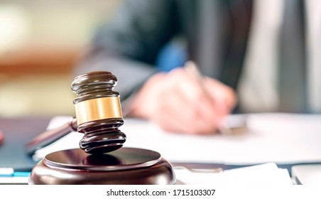 Closeup judge wooden gavel on sounding block with blur image of man hand writing on background.