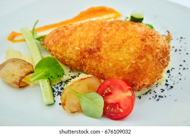 Close-up of juicy delicious breaded chicken cutlet with mashed potatoes on white plate closeup