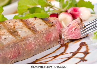 Closeup of juicy delicious Citrus-peppercorn-spiked grilled tuna steak with grilled vegetables. Shallow DOF