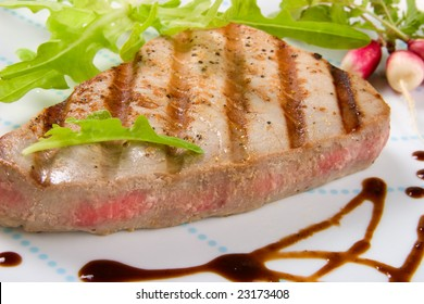 Closeup of juicy delicious Citrus-peppercorn-spiked grilled tuna steak with grilled vegetables.