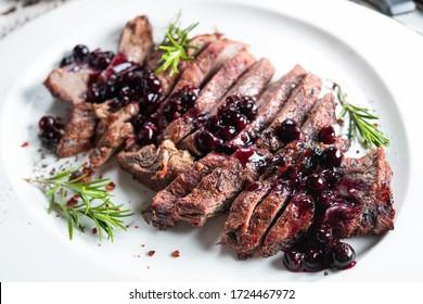 Die Juicy-Steak mit Rosmarin und Beerenmarmelade oder Sauce auf einem weißen Teller geschnitten. Kombination von Fett und süßen Lebensmitteln Hintergrund.