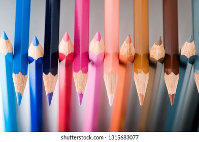 Close-up of juxtaposed colored pencil tips on a neutral gray background.