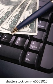 Close-up of keyboard,pen and dollars