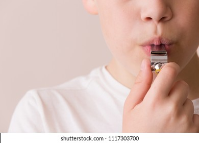 Closeup of kid boy's mouth with whistle.