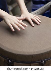 closeup of kid hands playing bongo