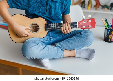 Close-up kid playing soprano ukulele sitting on desk. Preschool boy learning guitar at leisure. Concept of early childhood education and music hobby
