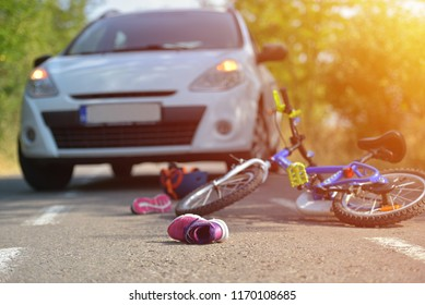 Close-up of a kid shoe fallen on the asphalt next to a bicycle after car accident on the street in the city