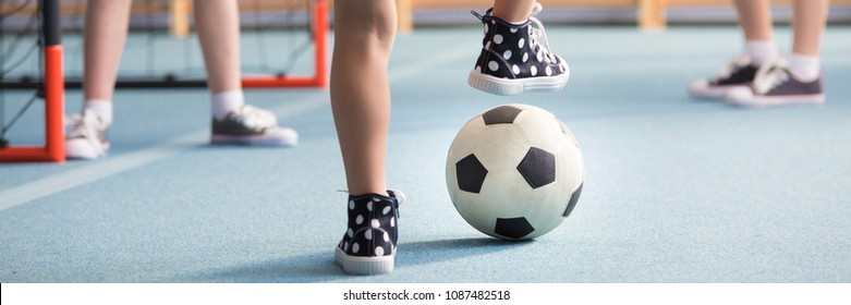Close-up of kid in sneakers playing football at school