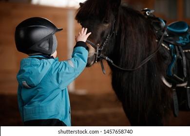 Gros plan sur un gamin faisant courir un cheval. Le garçon se prépare à apprendre l'équitation en saison froide. Hippothérapie pour le développement du bébé. Enfant en costume chaud et casque pour la sécurité. Sécurité d'abord